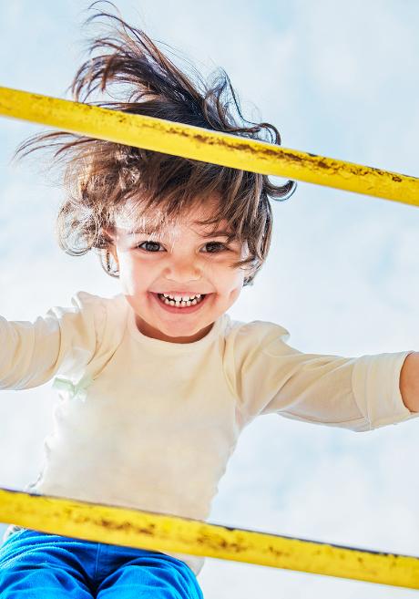 ein glückliches Kind spielt auf einem Gerüst draussen vor einer educcare Kindertagesstätte